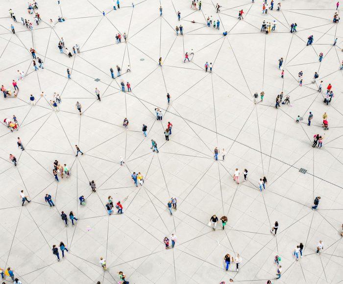 Menschen auf einem großen Platz, von oben fotografiert, die Menschen sind durch Linien auf dem Boden verbunden